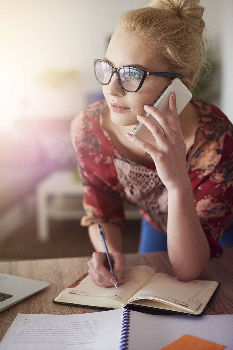 Woman holding phone and writing